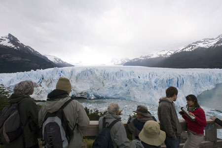 Tourists look at Argentina's Perito Moreno glacier near the city of El Calafate, in the Patagonian province of Santa Cruz December 15, 2009. Scientists warn that glaciers in the Andes, which limit Argentina with Chile are melting because of the effects of climate change. According to studies, these accumulations of ice are thawed at a pace so fast that it could disappear in 25 years.