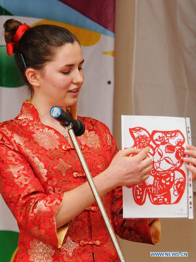 A Bulgarian student introduces her paper-cutting creation during the preliminary round of 'Chinese Bridge' competition in Sofia, Bulgaria, may 17, 2012.