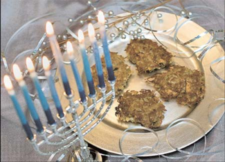 Oven-crisped potato latkes on a plate next to a menorah. Everyone loves latkes and the sight of those beautiful menorah candles lighting up a dark winter's night.